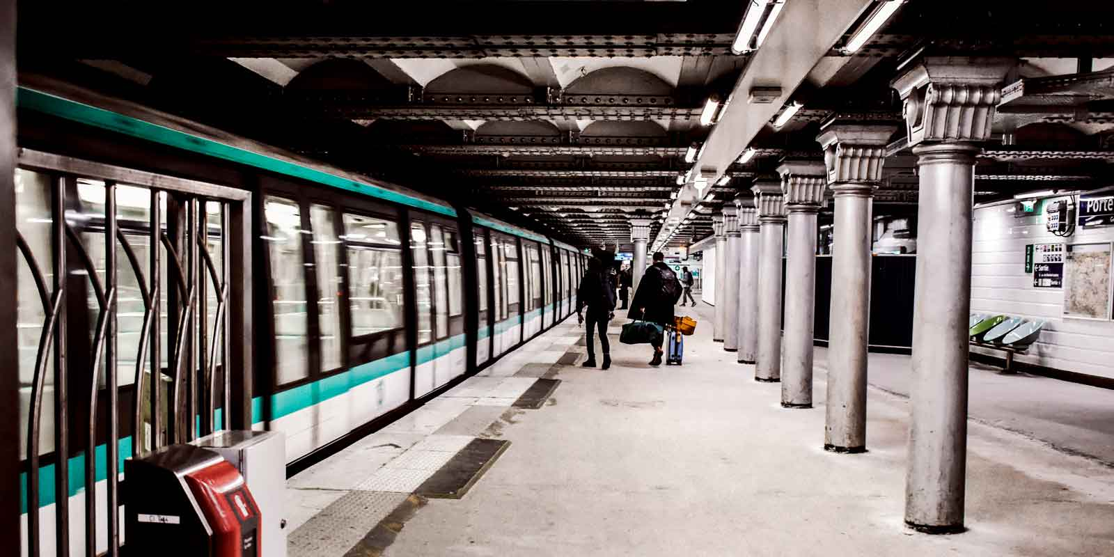 A Paris Metro train pulls into a train station while a few people wait to board.