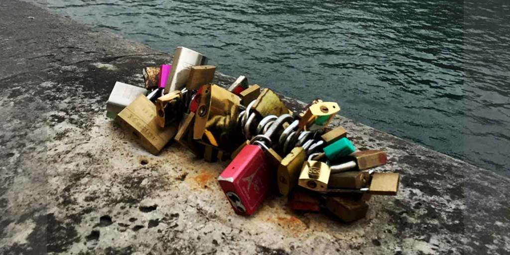 Close up photograph of a bunch of padlocks, also known as love locks, attached to a piece of a wall along the Seine River in Paris, France.