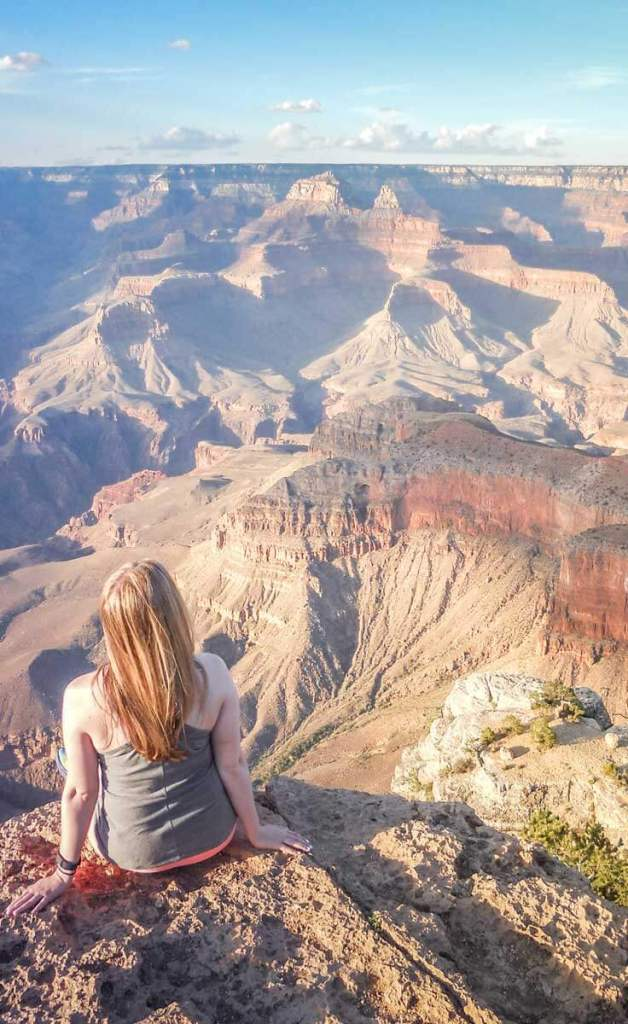 Woman sits on a ledge overlooking the Grand Canyon in Arizona.