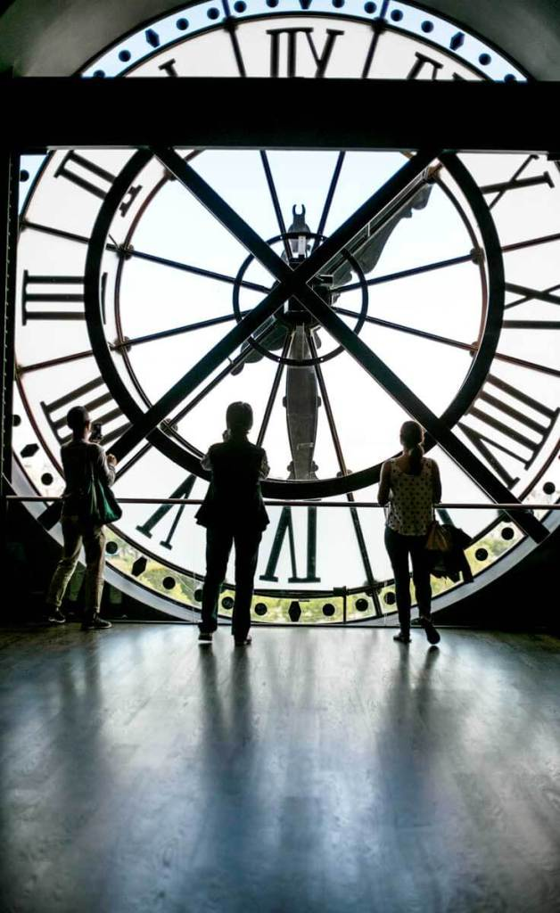 Photograph of the inside of the clock window at the Musée d'Orsay in Paris France, with silhouettes of 3 people admiring the view.