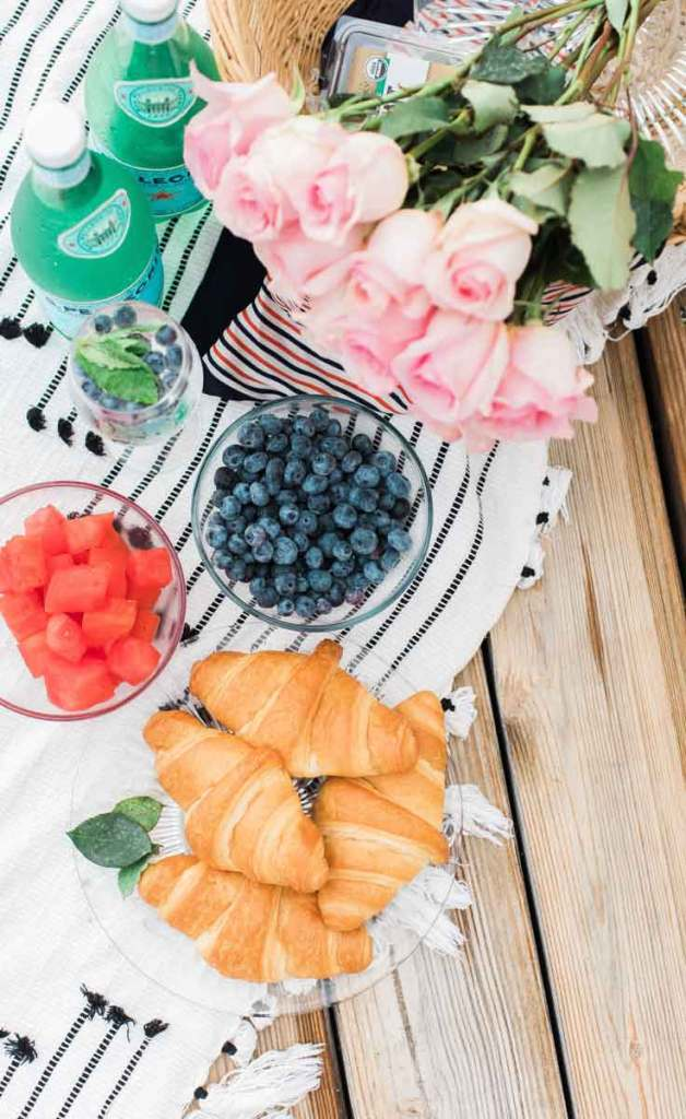 Flat lay photograph of a picnic spread, featuring a plate of croissants, a bowl of watermelon chunks, a bowl of blueberries, 2 bottles of San Pellegrino, a basket of pink roses, all on top of a white blanket with black stripes spread over a picnic table.