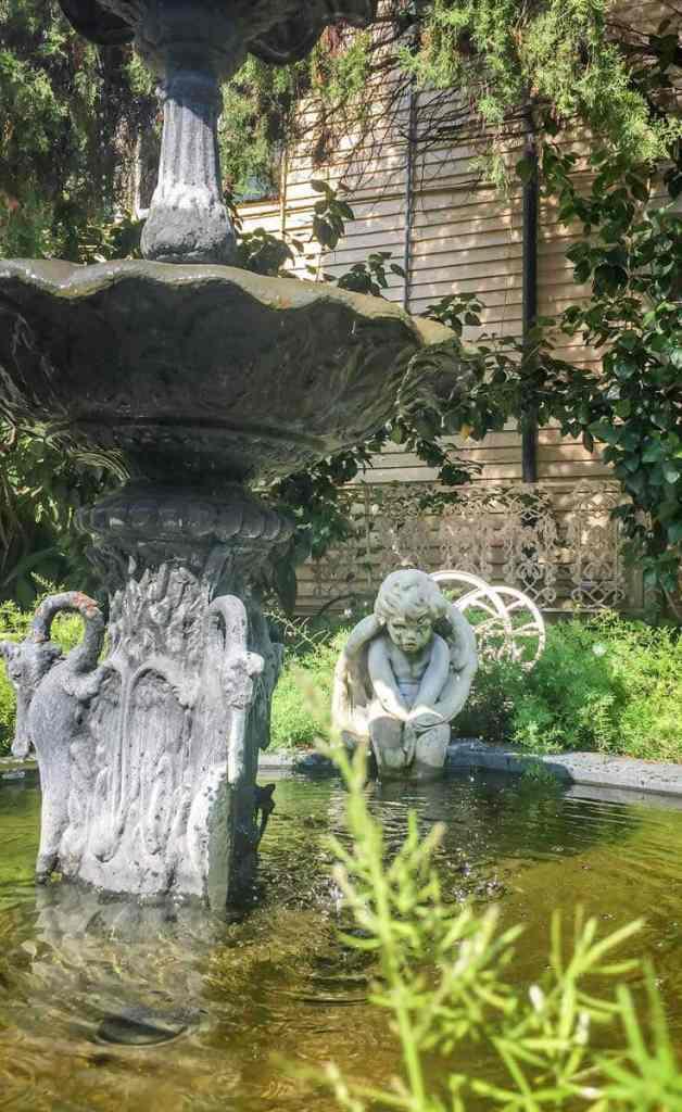Closeup of a water fountain outside the Cornstalk Hotel, with a sullen cherub statue in the background.
