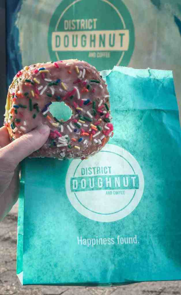 Closeup of a sprinkle-covered doughnut with a teal blue bag from District Doughnut in DC.