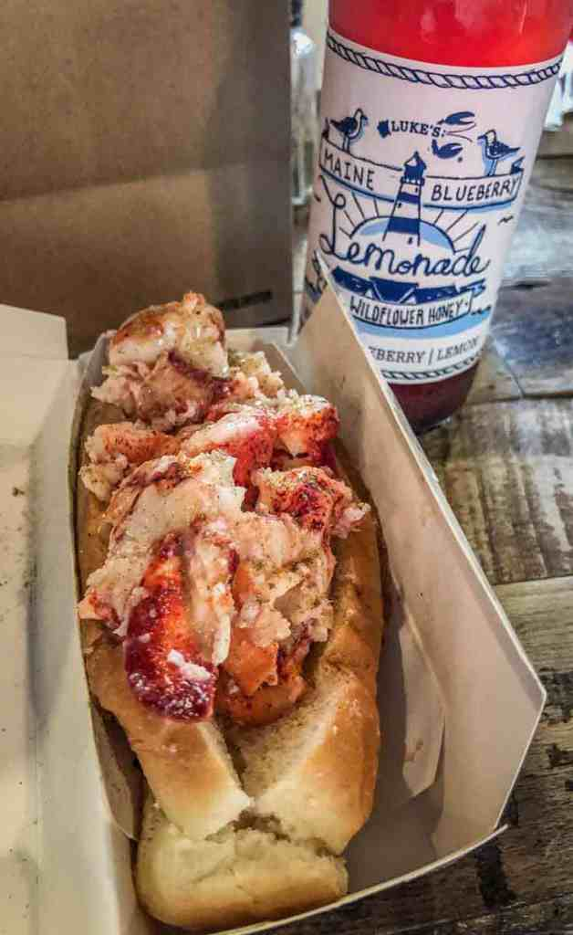 Closeup of lobster salad in a hot dog bun with a bottle of blueberry lemonade in the background.