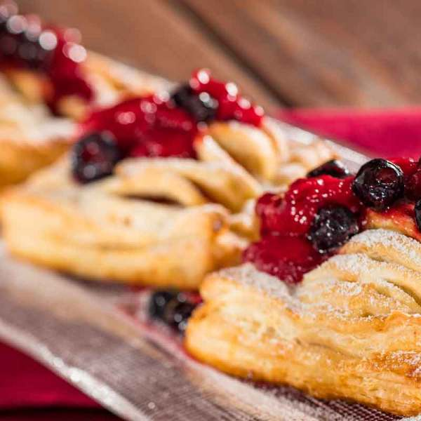 Closeup photograph of mini cheese strudels with berries spooned on top.