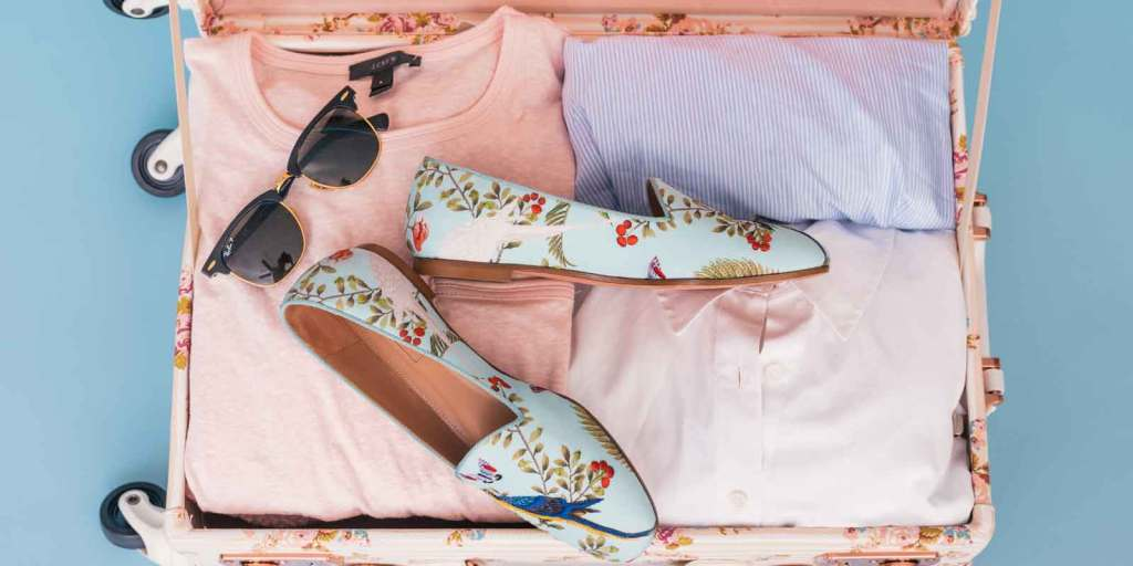 Flat lay photograph of a pastel floral suitcase filled with pink and light blue tops, sunglasses, and blue floral flats.
