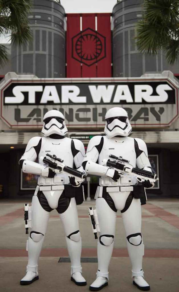 Two Star Wars stormtroopers stand in front of the entrance of Star Wars Launch Bay.
