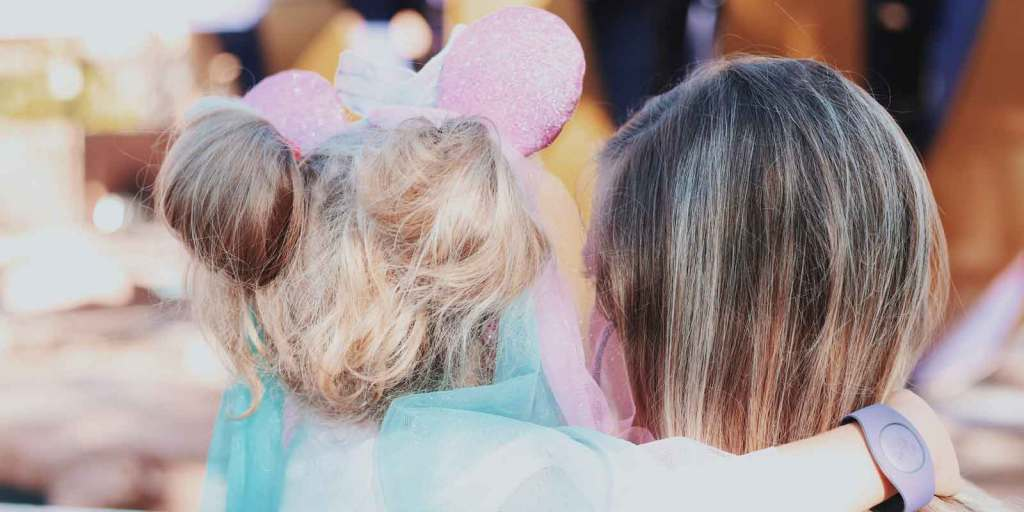 Photograph of a woman holding a young girl wearing a light pink Minnie Mouse ears with pink and blue flowing chiffon train.