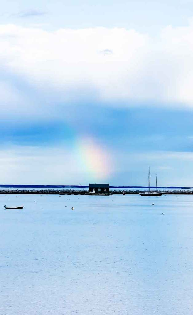 Landscape view of the ocean in Provincetown and a rocky patch of land with a small shack. The sky is bright blue with a rainbow stretching out of a cloud above the shack.