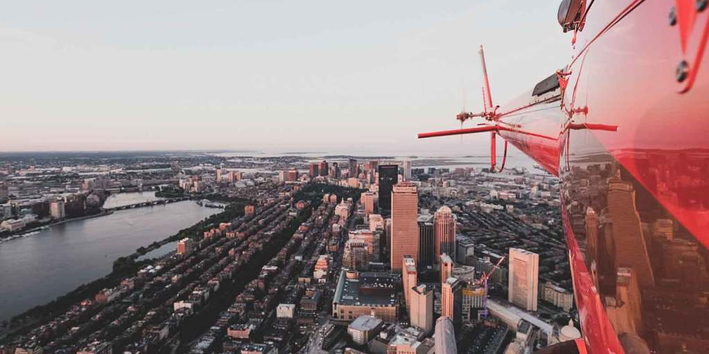 Aerial view of Boston and the Charles River with the tail view of a red helicopter in the corner.