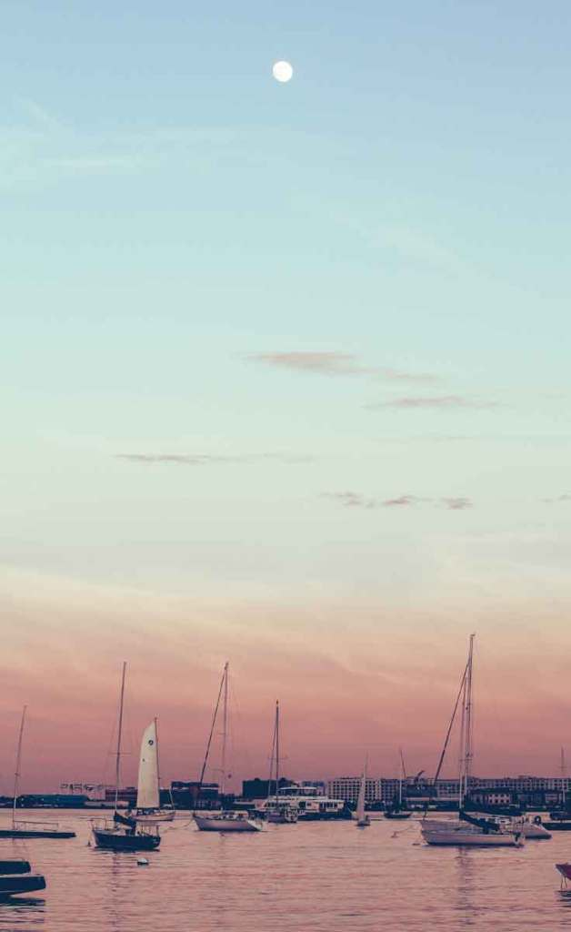 Sailboats along the Boston Harbor with the city of Boston in the background. The sky is light blue, fading to pinkish orange.