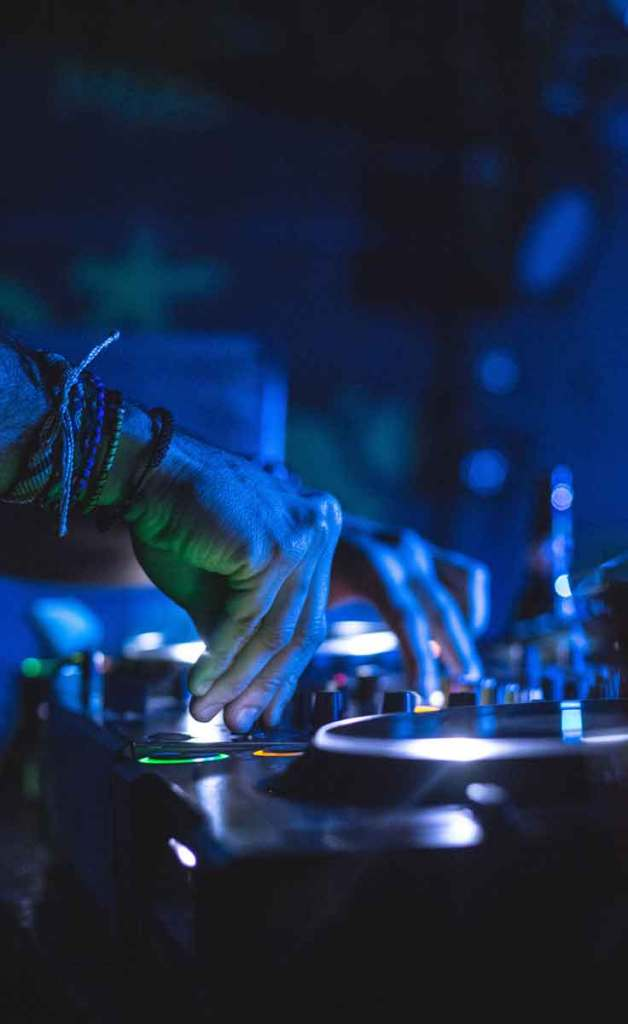 Closeup of a man using DJ turntables in the dark.