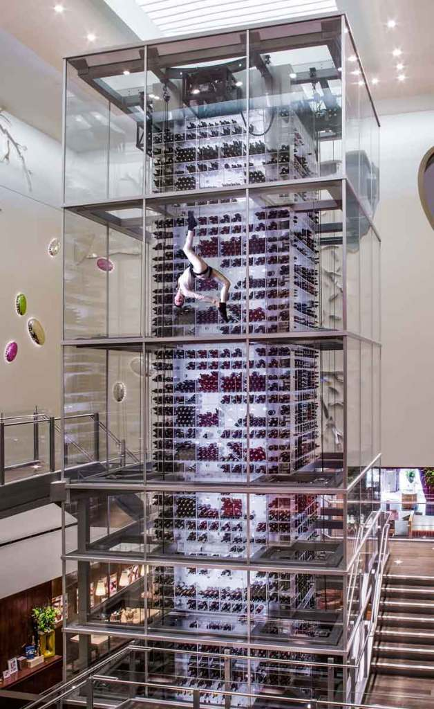 Photo of the massive tower of wine enclosed by glass at Aureole at Mandalay Bay. A woman is suspended from the top in a harness in an acrobatic pose.