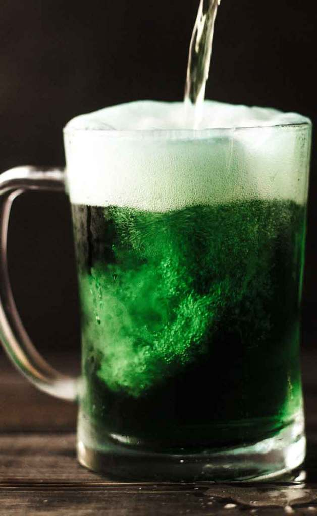 Close up photograph of a mug of green beer being poured.