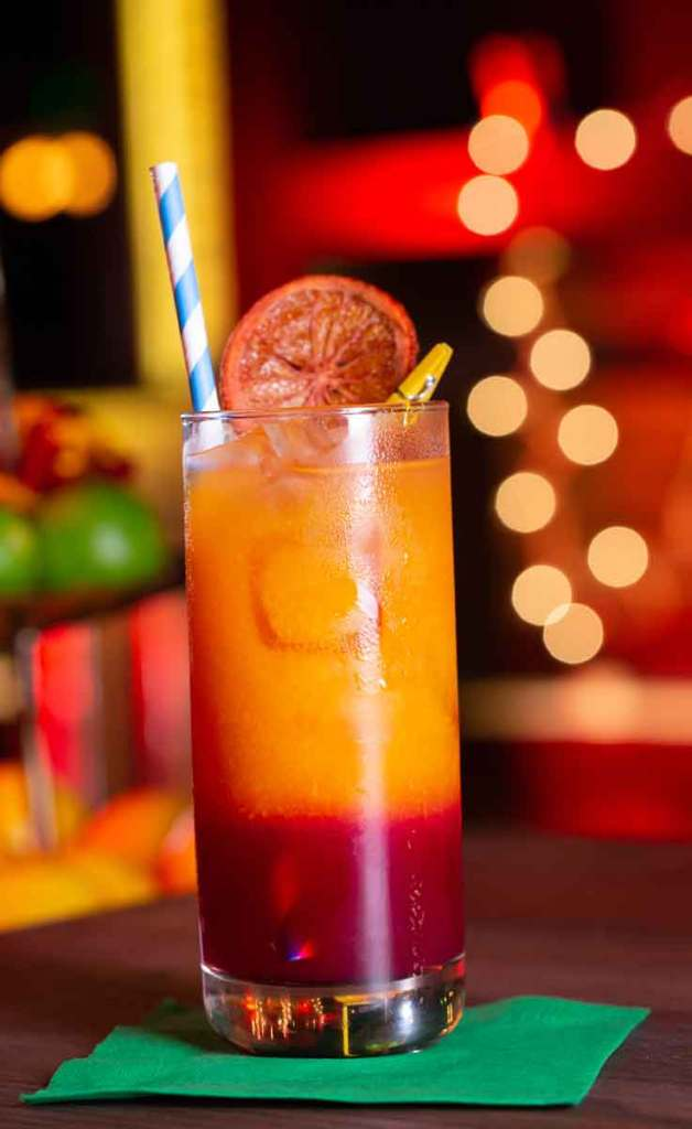 Closeup of a highball glass filled with a cocktail that is cherry red at the bottom and orange at the top, garnished with a dried blood orange and a blue and white striped paper straw.