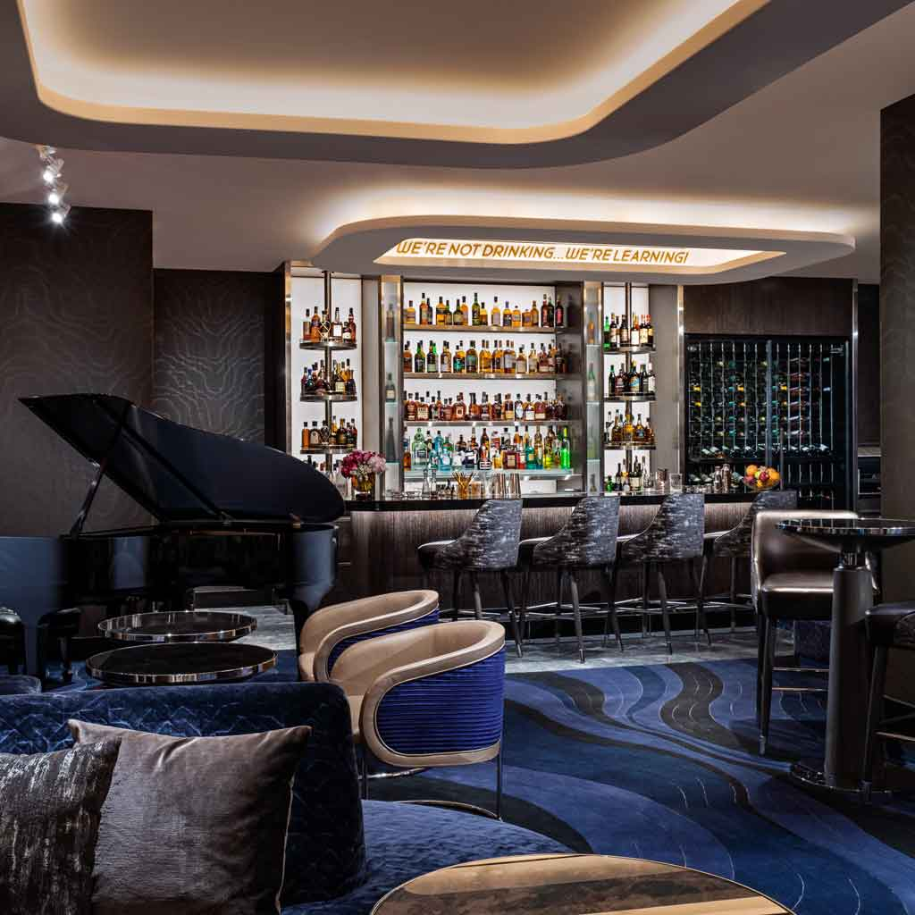 "Photograph of Mr. COCO lounge and restaurant, with dark grey and cobalt blue decor, a Steinway piano, and a bar filled with prime liquor. A sign says ""We're not drinking...we're learning!"""