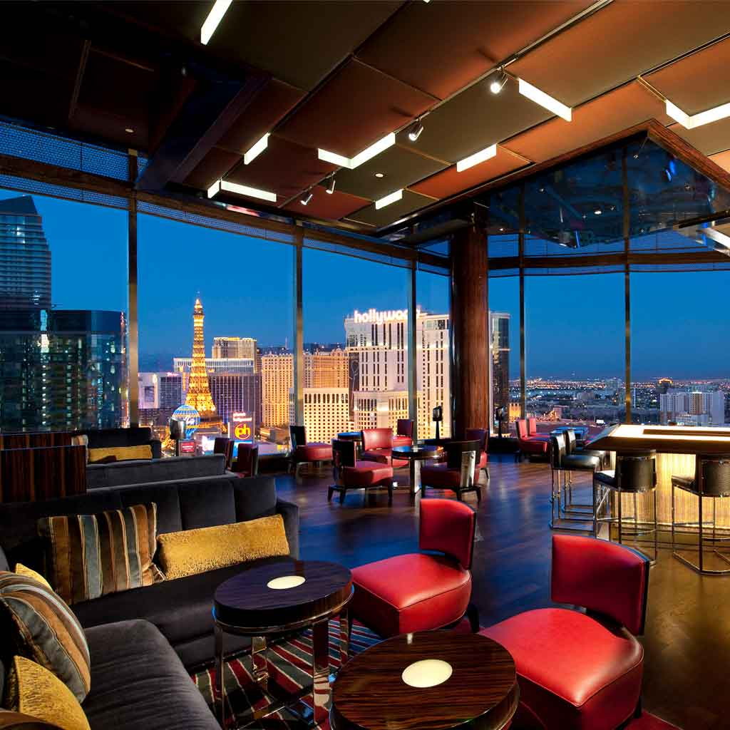 Photograph of an empty SkyBar with the Las Vegas skyline seen through the ceiling to floor windows in the background.