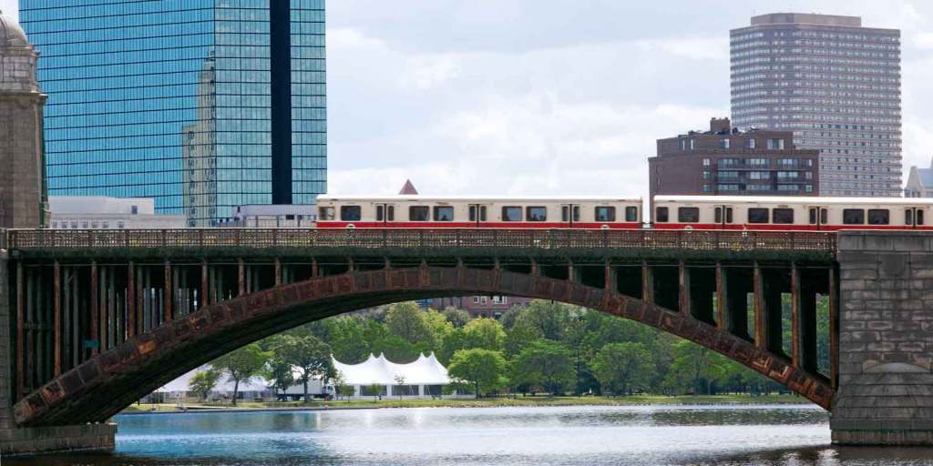 Landscape view of the Red line train crossing a bridge over the Charles River between Boston and Cambridge, MA. Using public transportation in Boston is cheaper AND more convenient than driving in Boston.