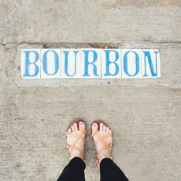 "Photograph pointing down to the ground, showing a woman's feet in sandals and tiles embedded in a sidewalk that spell out ""Bourbon."""