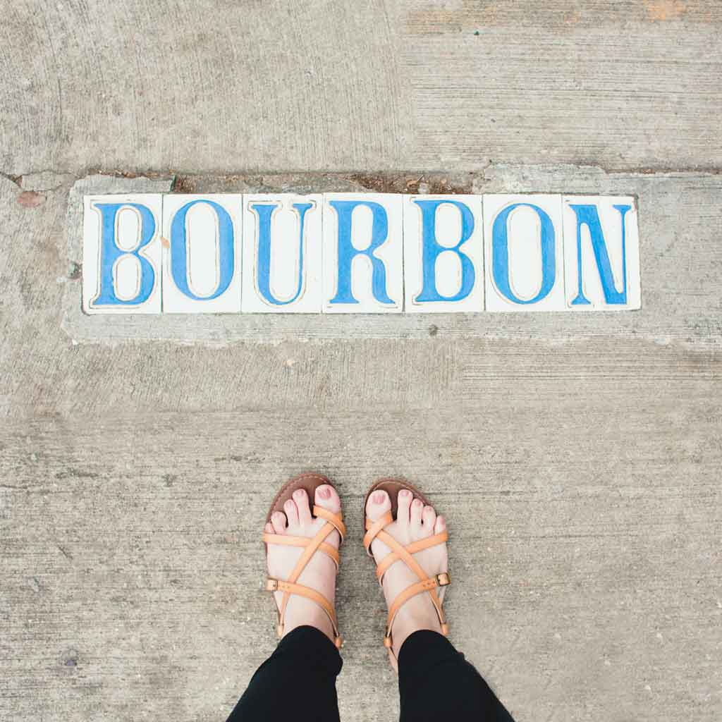 """Photograph pointing down to the ground, showing a woman's feet in sandals and tiles embedded in a sidewalk that spell out """"Bourbon."""""""