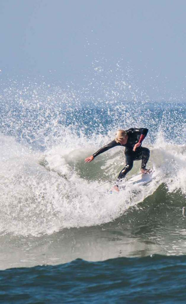Man in a black wetsuit surfing a big wave in Surf City USA, aka Huntington Beach, California.