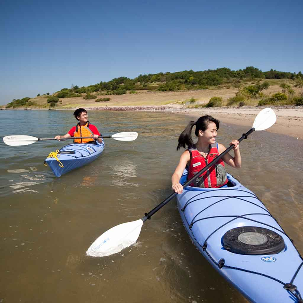 A man and woman kayaking off the coast of one of the Boston Harbor islands.