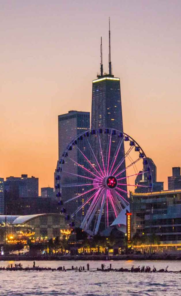 Closeup of the beach along Lake Michigan in Chicago during sunset, with tall buildings and a ferris wheel in the background.