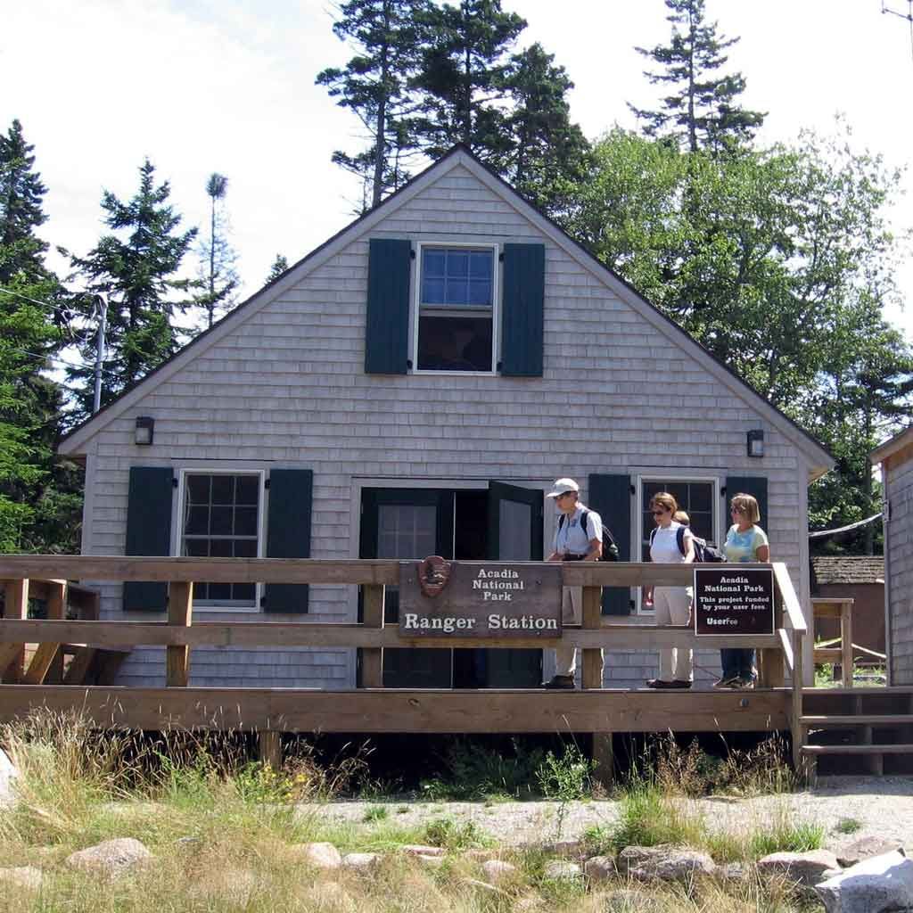 """A small cottage-like building with a sign that says """"Acadia National Park Ranger Station."""""""