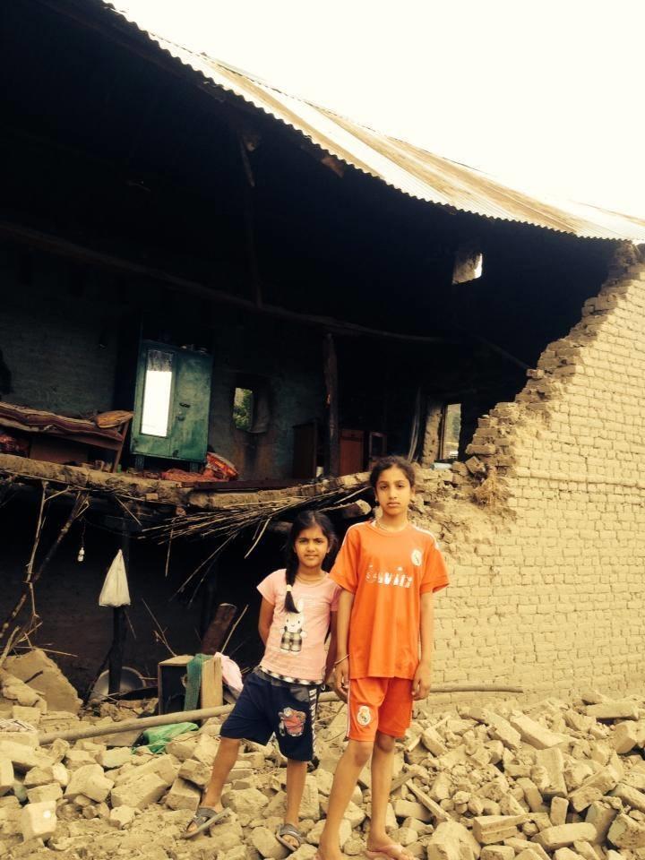 Les fillettes devant ce qu'il reste de leur maison.