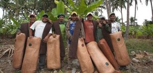 Men in another country holding bags of fruit