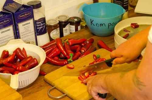Här förbereder jag ett par kilo Espelette för torkning. Nyskördad chili till vänster. Kompostbehållare och torkolla till höger.