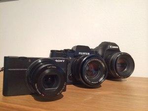 Grössenvergleich der Fuji X-T1 mit der EOS 5D MKIII und der Sony RX100. Ansicht schräg.