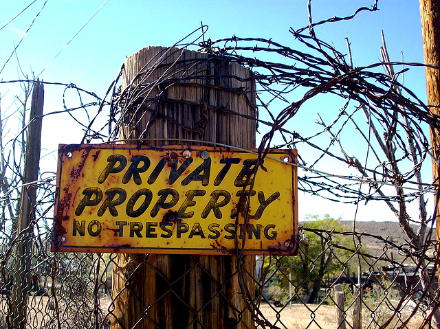 Private property sign with barbed wire fence