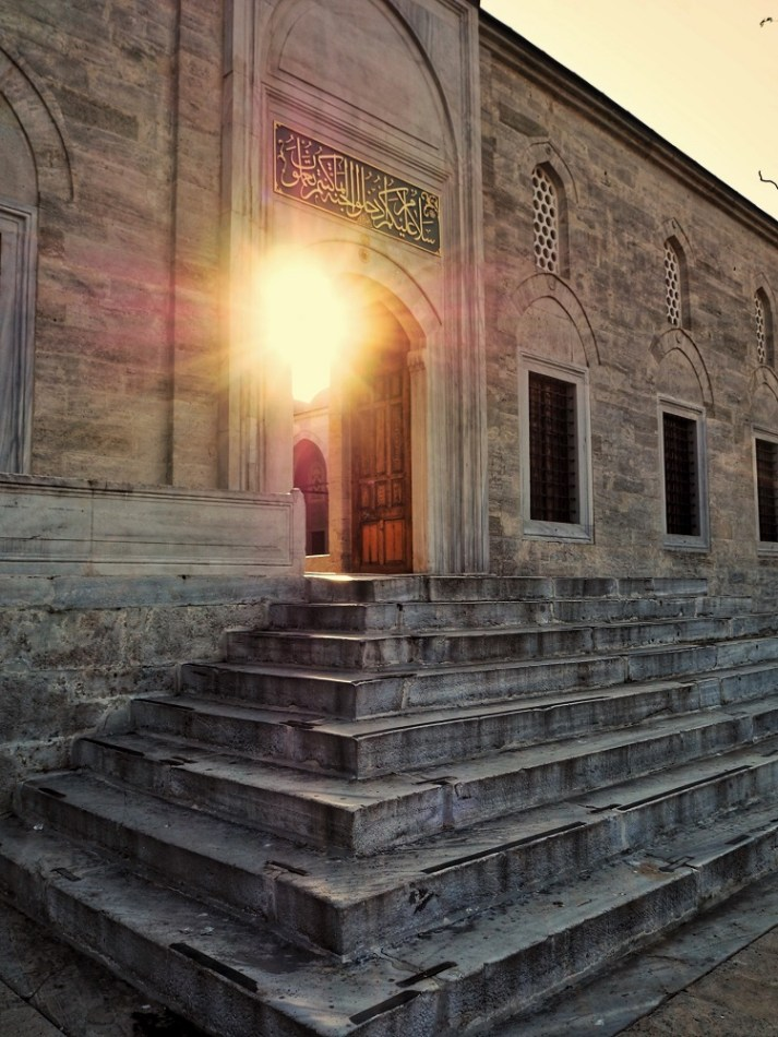 Sunlight shines from inside a mosque courtyard.