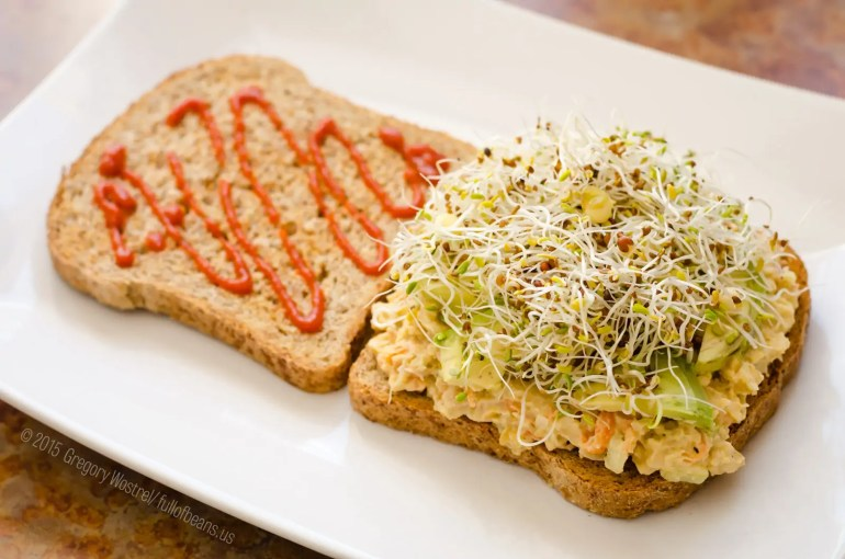 """Better Than Tuna"" on toast with avocado slices, mixed sprouts and Sriracha hot sauce."