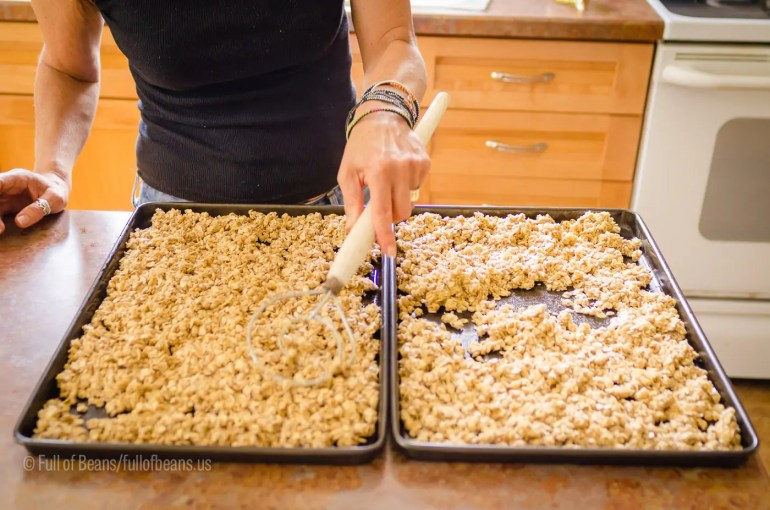 Spreading the granola on cookies sheets for cooking