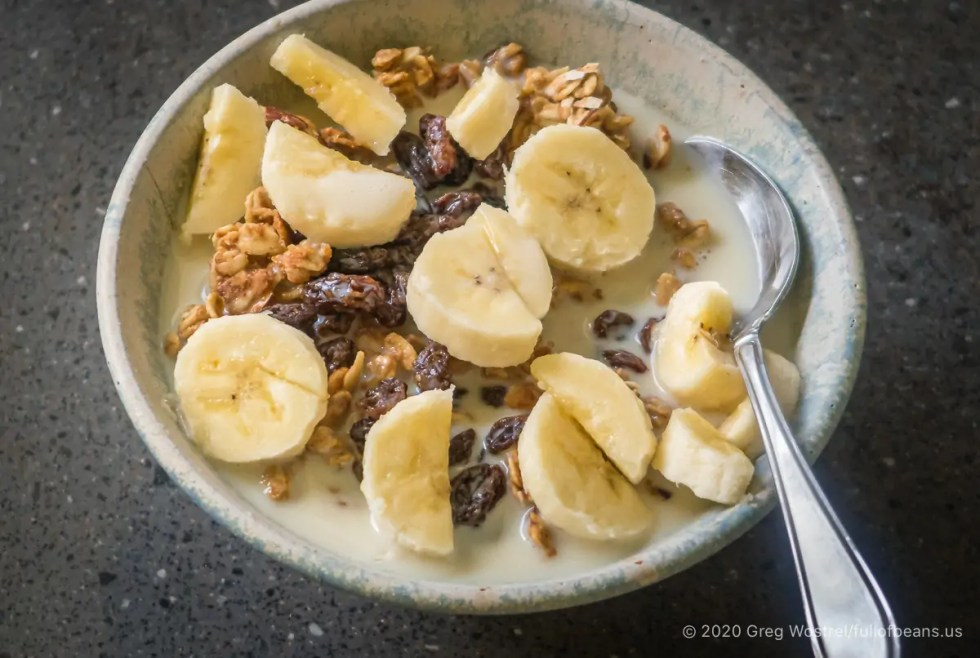 easy almond maple granola in a bowl with bananas and raisins