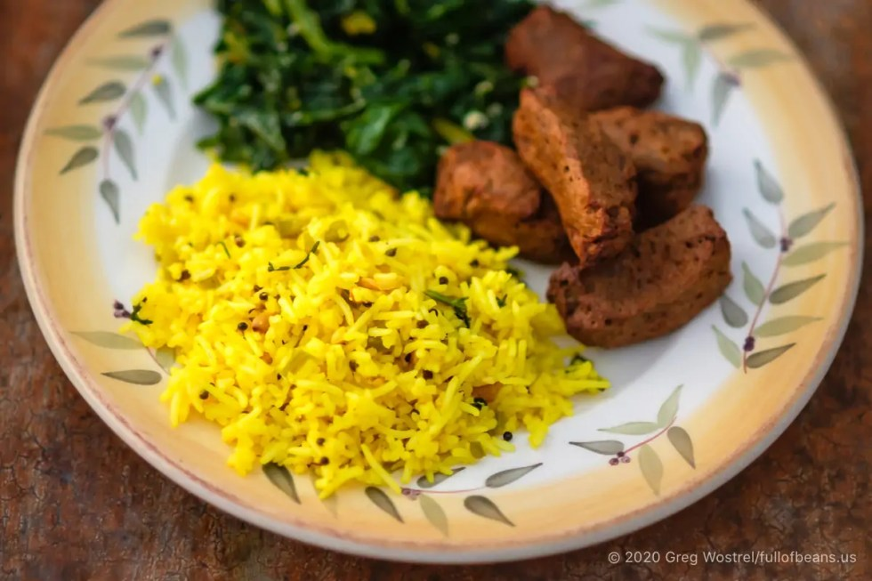 Lime and Cashew Rice Pilaf plated with sautéed greens and grilled savory seitan