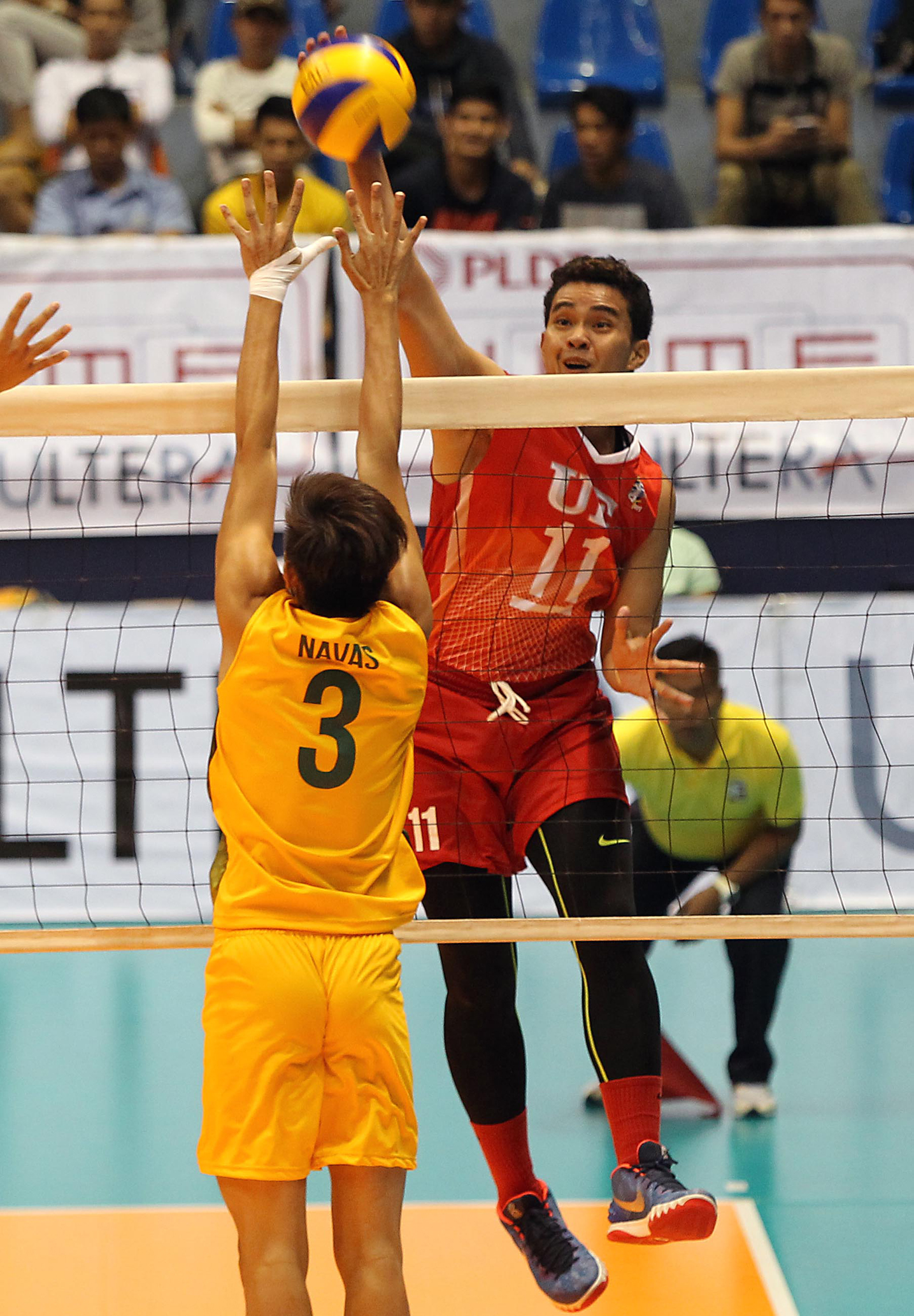 UE's Edward Camposano scores on a power tip against FEU's Jesser Navas during their Spikers' Turf clash at The Arena.
