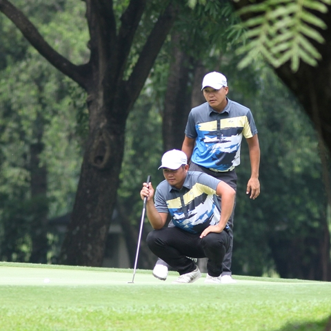 South's Clyde Mondilla (foreground) and Charles Hong check the line of their putt on No.1 in their match up against Miguel Tabuena and Benjie Magada of Team North.