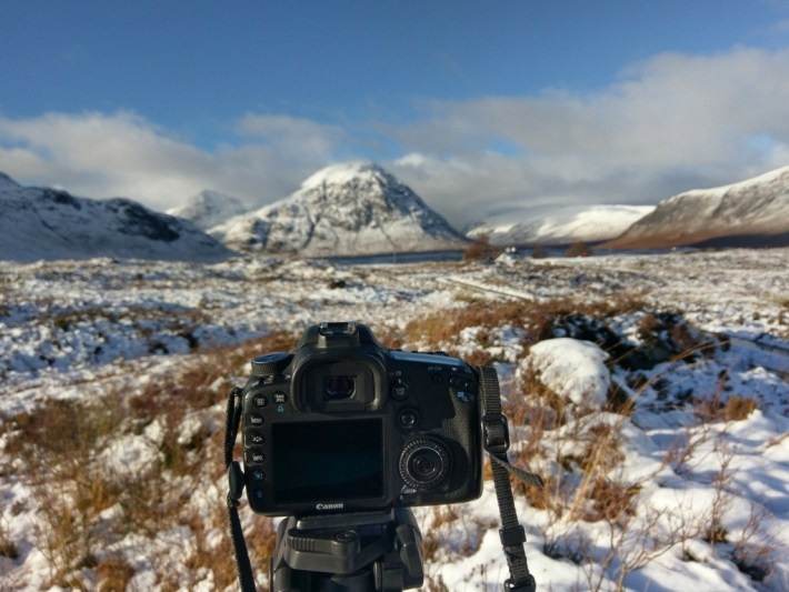 Photography, Scotland. Camera set up on tripod in front of snowy mountain