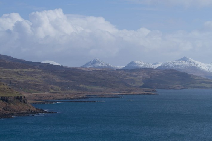 Snow capped mountains in the background and a sea loch in the foreground