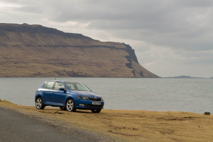 Photo of a car beside a sea loch on the Isle of Mull. Large cliffs in the background