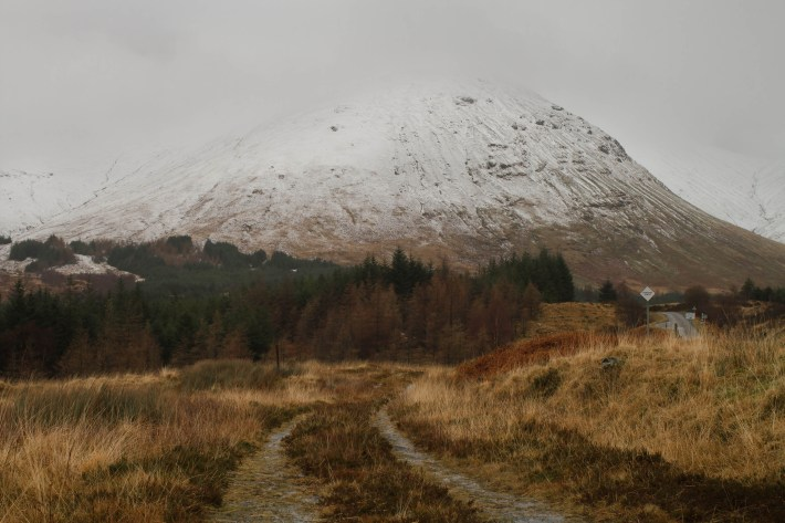 Snow capped mountain on the isle of mull. A vehicle track down the centre of the photo going off in to the distance