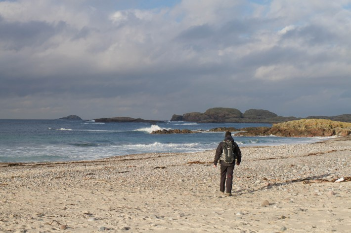 Photo of a man walking across the beach. The sun is shining and the waves are crashing on the rocks