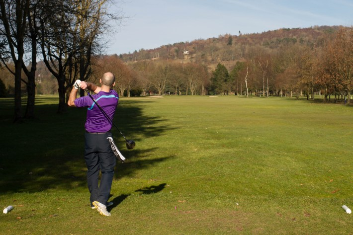King James VI Golf Course, Perth, Scotland Travel Guide. Golfer with a club in his hand after hitting the ball. Fairway, bare trees and a hill