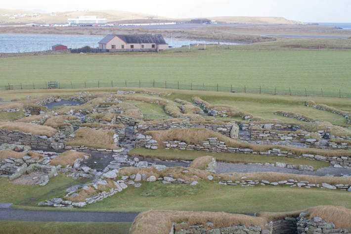Photo of Jarlshof. A prehistoric and Norse site in Shetland. Remains of a long house - stones showing in the grass