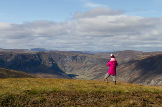 Photo of a female figure stood on top of a hill looking out at the view