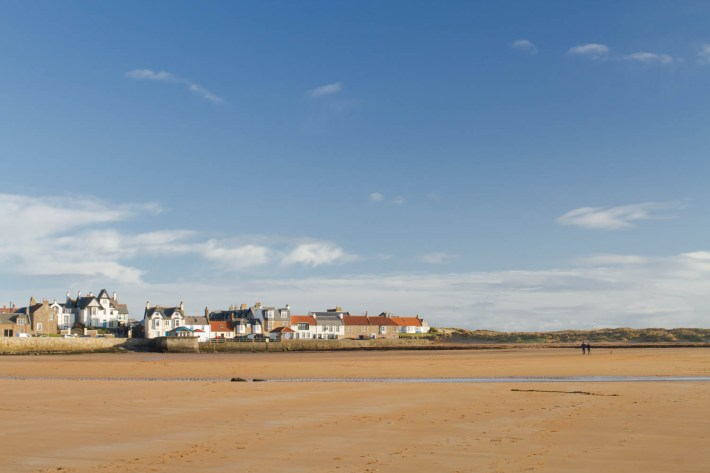 Elie Beach, Fife, Scotland. Wide photo of Elie beach. Long stretch of sand with people in the distance. A row of large properties and sky with whispy clouds