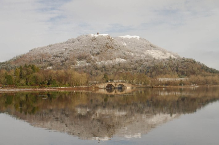 Inveraray, Argyll, Loch Fyne, Scotland. A dusting of snow on the hill. The trees are bare as it is winter. There is a small bridge over the water and the reflection in the foreground is perfectly still